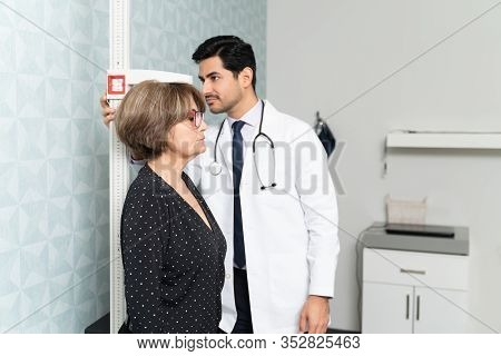 Hispanic Male Physician Measuring Height Of Senior Woman In Hospital