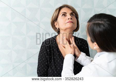 Caucasian Woman Visiting Female Geriatrician For Thyroid Checkup