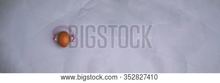 Easter Egg With Pink Headphones On Gray Background With Copyspace And Text. Banner Of Macro Moody Mi