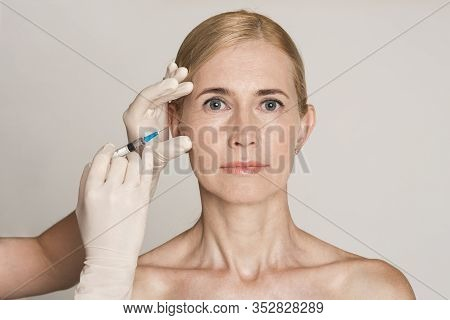Plastic Surgery. Blonde Middle-aged Woman Receiving Botox Injection In Beauty Clinic Isolated On Gra