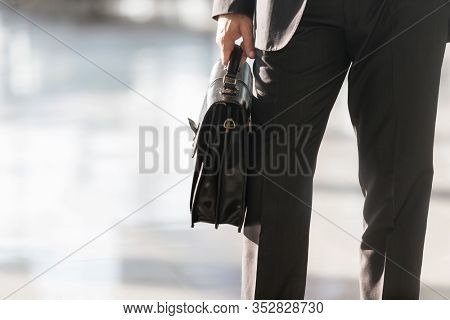 Cropped image of businessman holding briefcase bag in airport