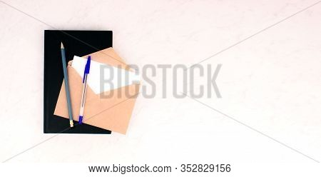 Notebook, Pen, Pencil, Envelope And Letter White Card Flat Lay On Marble Background. School And Offi