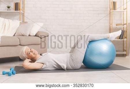 Back Strengthening. Happy Active Senior Woman Doing Exercises With Fitness Ball At Home, Free Space