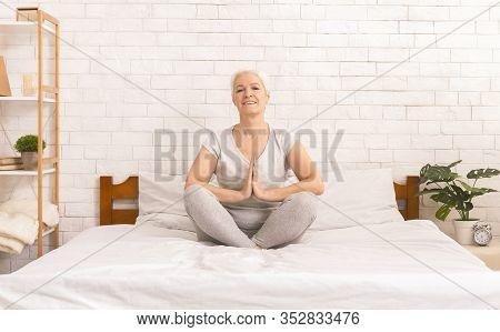 Anti-stress Yoga. Senior Lady Meditating In Lotus Position On Bed, Padmasana