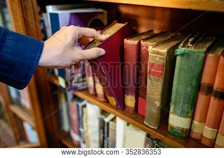 Male University Student Hand Choosing And Picking Vintage Book From Old Wooden Bookshelf In College