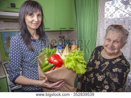 Humanitarian Assistance To A Pensioner From A Social Worker;  Woman Assisting Elderly Lady With Her