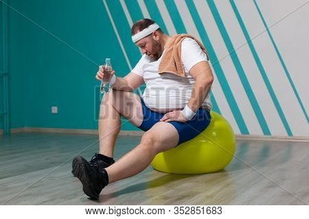 Overweight Man Is Sitting On A Fitness Ball Exhausted After A Hard Training In Group Fitness Classes