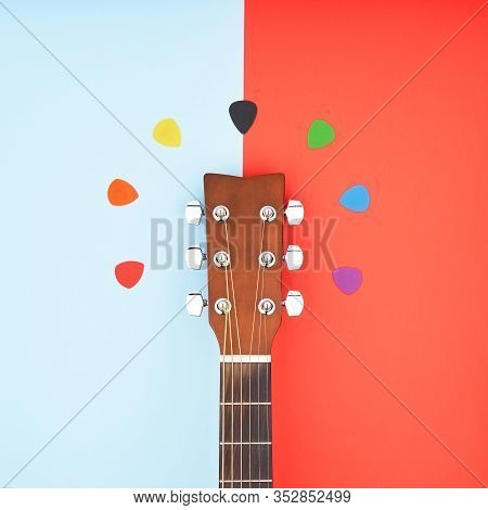 Colorful Picks Around Acoustic Guitars Headstock. Flat Lay On Light Blue And Red Background