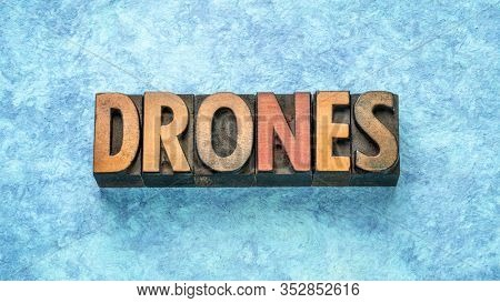 drones word abstract in vintage letterpress  wood type against blue textured paper, technology concept