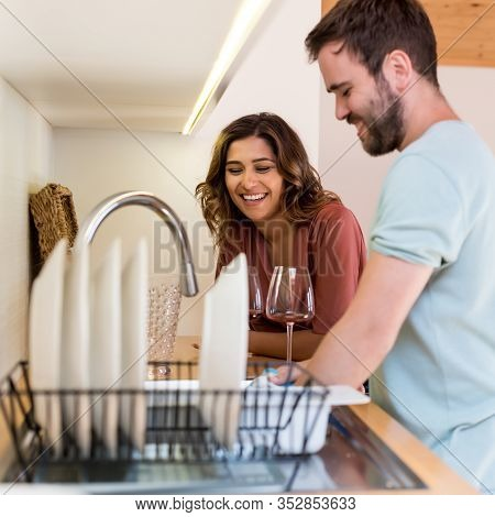 Happy Woman Watching Man Washing Dishes.