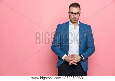 Confident smart casual man taking a tough decision while wearing glasses and standing on pink studio background