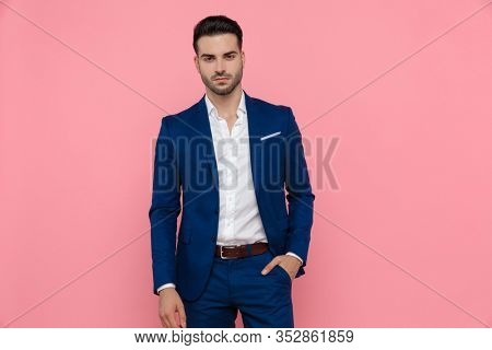 Tough businessman holding his hand in his pocket while wearing blue suit and standing on pink studio background