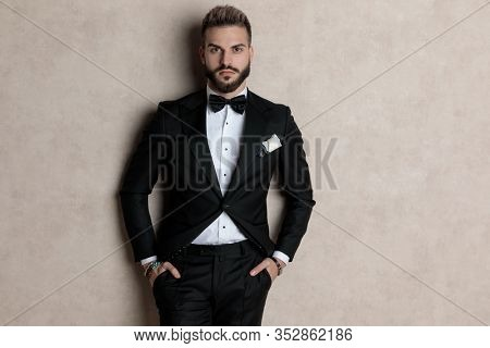 Bothered groom looking forward with both hands in his pockets while wearing tuxedo and standing on wallpaper studio background