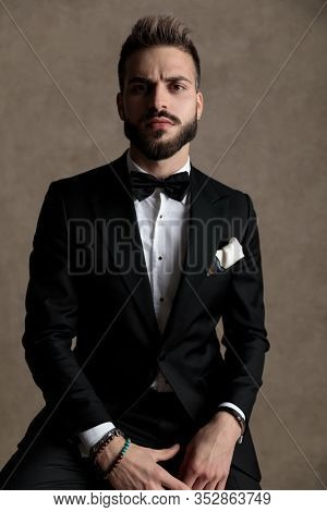 Bothered groom looking forward and frowning while wearing tuxedo and sitting on a stool on wallpaper studio background