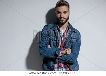 Bothered fashion model holding his arms folded at his chest and looking forward while standing on gray studio background