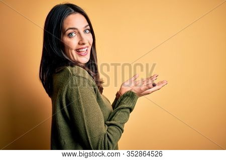 Young brunette woman with blue eyes wearing green casual sweater over yellow background pointing aside with hands open palms showing copy space, presenting advertisement smiling excited happy