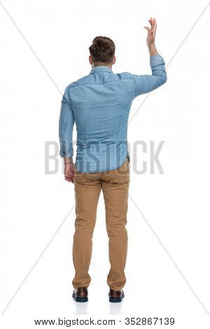 Rear view of a bothered casual man arguing and gesturing, standing on white studio background