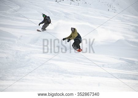 Two Freeriders Sliding Down The Mountain Slope