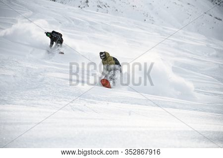 Two Freeriders Slipping Down The Mountain Slope