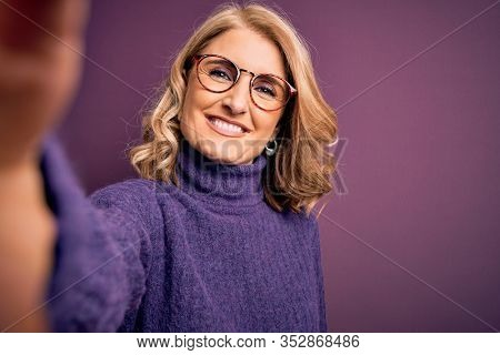 Middle age beautiful blonde woman wearing sweater and glasses make selfie by the camera with a happy face standing and smiling with a confident smile showing teeth