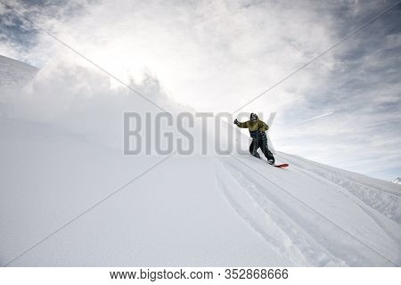 Freerider In Anorak Rides On A Snowboard In Mountains