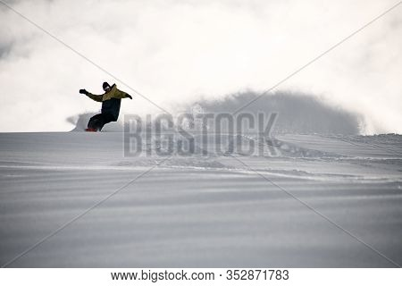 Freerider In Sportswear Sliding On A Snowboard In Mountains