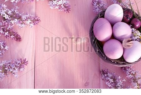Colorful easter eggs in basket on rustic wooden table.Holiday background with spring lilac flowers. Top view with copy space