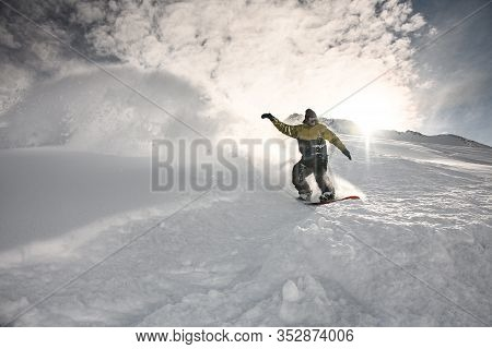 Male Freerider Slipping On Board On Snowy Mountain