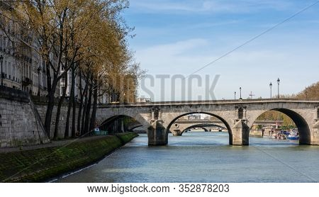 Paris, France, March 30, 2017: Paris Bridge. Bridges of Paris over Seine River, on a beautiful cloudy day. No less than 37 bridges span Seine, river that separates Left and Right banks of Paris