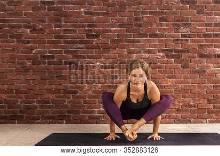 Sporty Woman Doing Difficult Pose, Astavakrasana, Asymmetrical Arm Balance Eight Angle Pose. Lady In