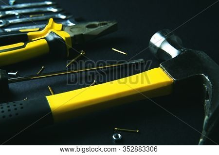 Construction Tools For Home Renovation On Black Background. Close Up Image Of Yellow Hammer, Pliers,