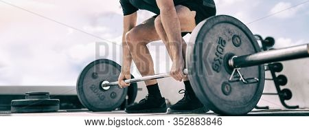 Weightlifting deadlift panoramic banner of fit man bodybuilding powerlifting at outdoor gym header. Bodybuilder doing barbell weight workout with heavy bar.