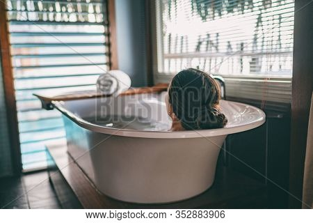 Bath taking woman relaxing in bathtub of hotel room at luxury overwater bungalow resort in Bora Bora, Tahiti.