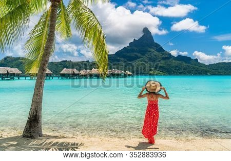 Luxury beach vacation travel destination tourist woman walking on Bora Bora island enjoying holiday in Tahiti, French Polynesia with Mount Otemanu and overwater bungalows villas hotel landscape.