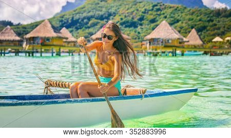 Beach sport tourist woman paddling in outrigger canoe Tahiti activity. Vaa French polynesia polynesian watersport.