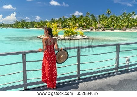 Bora Bora luxury resort vacation woman at honeymoon destination hotel by ocean beach. Bora Bora island relaxing tourist elegant lady walking at Tahiti, French Polynesia travel for summer vacations.
