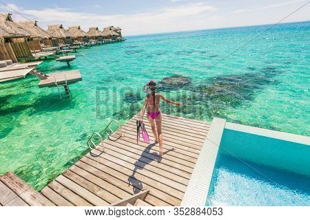 Luxury overwater bungalow Tahiti resort woman enjoying snorkeling from private villa balcony. Travel vacation hotel in Bora Bora, Tahiti, French Polynesia. Watersport fun activity.