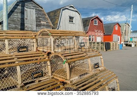 Lobster traps piled up against the bait sheds on a wharf in rural Prince Edward Island, Canada,