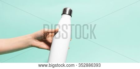 Close-up Of Female Hand Holding White Reusable Steel Stainless Eco Thermo Water Bottle Isolated On B