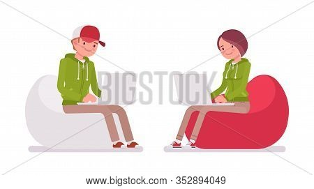 Young Man, Woman Sitting In A Bean Bag Working With Laptop, Wearing Hoodie Jacket. Cute Smart People