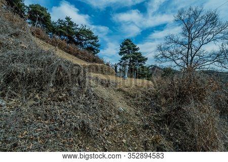 Boeun, South Korea; February 24,2020: Marked Grave Site On Mountainside Under Partly Cloudy Blue Sky