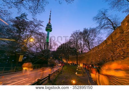 Seoul Tower In Seoul City At Night View In Spring With Cherry Blossom Tree And Old Wall With Light A