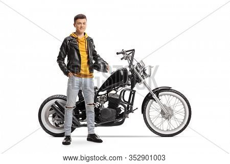 Full length portrait of a young guy holding helmet and posing next to a custom motorbike isolated on white background