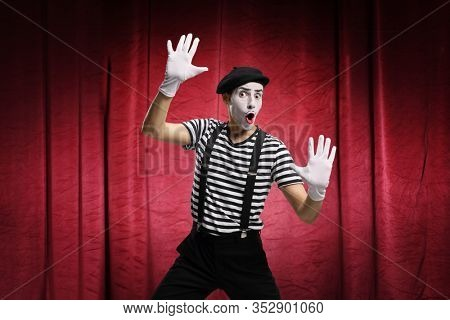 Mime pretending to touch an imaginary glass on stage