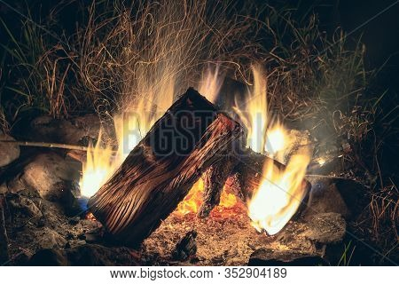 Bright Night Bonfire Among Grass And Stones. Beautiful Bonfire With Flying Sparks Pattern