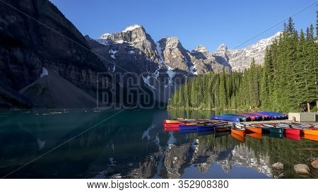 Wide View Of Moraine Lake And Canoes In Canada On A Summer Morning