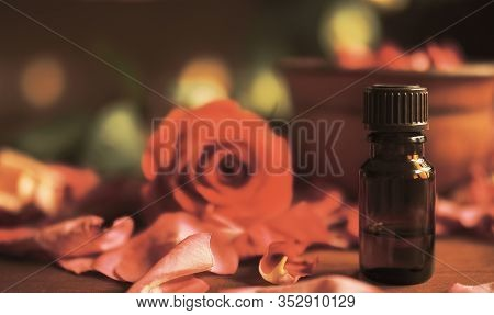 Aroma Oil Dark Glass Bottle, Rosebud And Rose Petals On The Wooden Table, Toned Warm, Selected Focus
