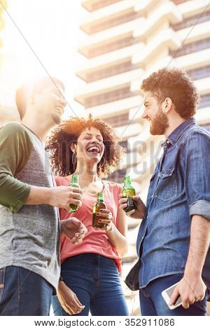 Laughing friends make small talk with a bottle of beer at a party on a rooftop