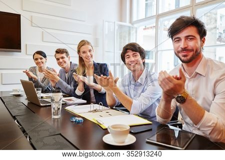 Satisfied team gives applause at the business meeting in the conference room