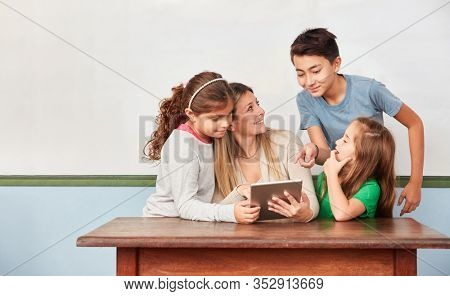 Teacher and elementary school students with tablet computer learn media literacy